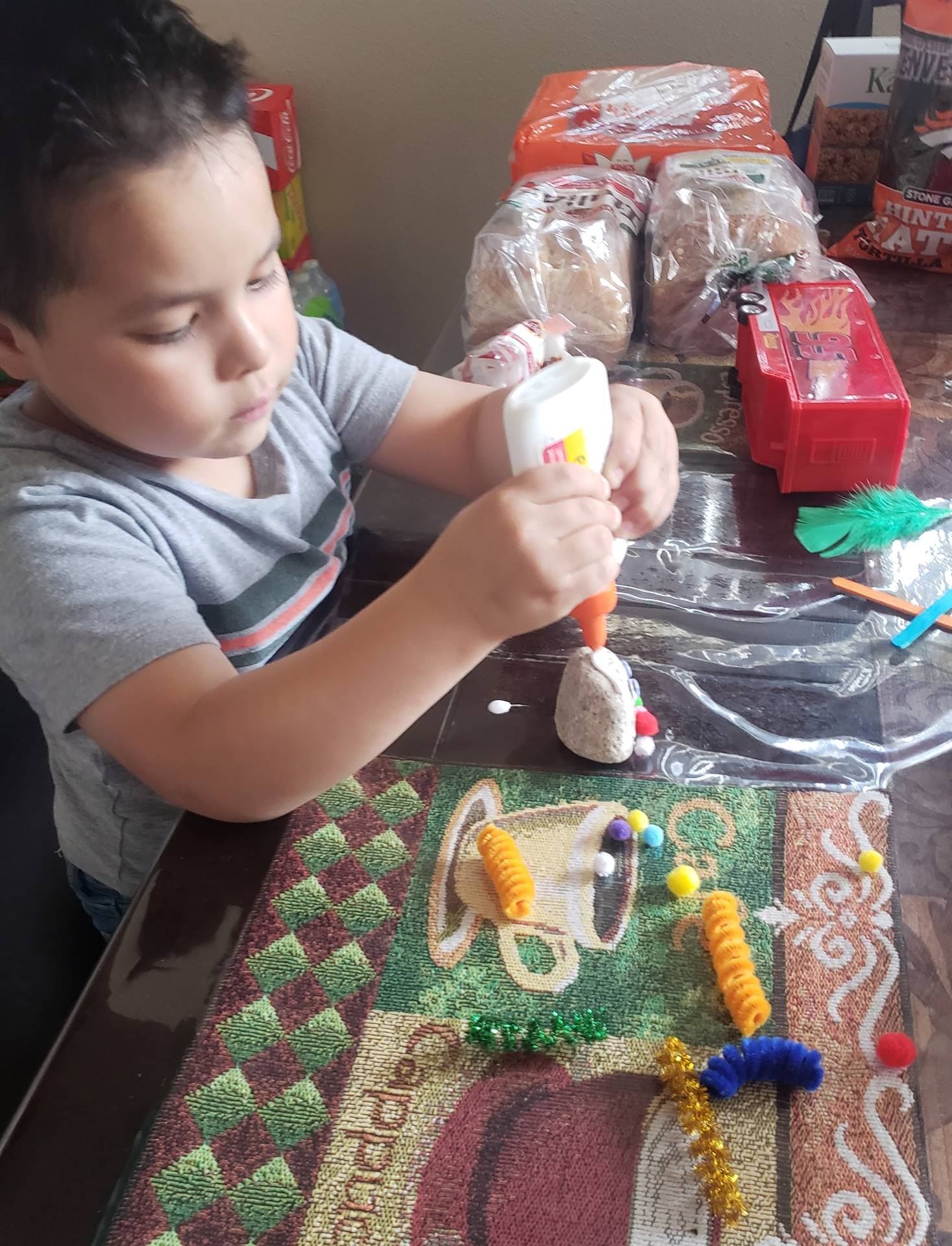 A little boy is gluing his pet rock together.