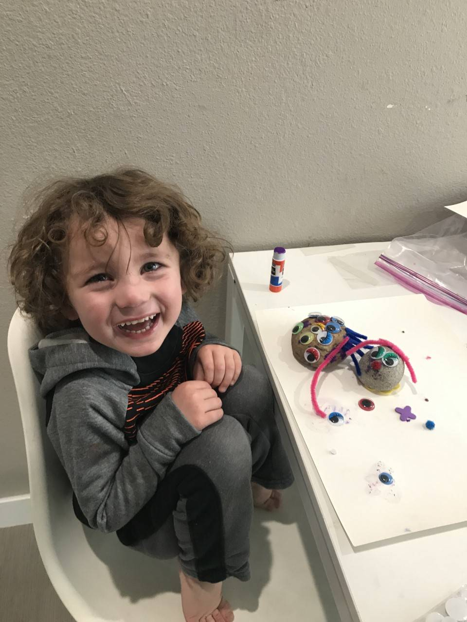 A student smiles with his pet rocks he made.