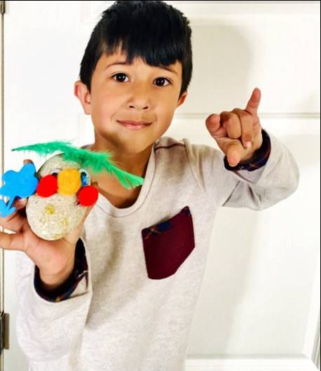 A student holds up his pet rock he made.