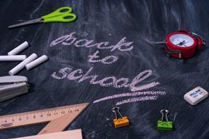 Blackboard with chalk and green scissors