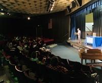 Principal Speaking on Stage in Auditorium